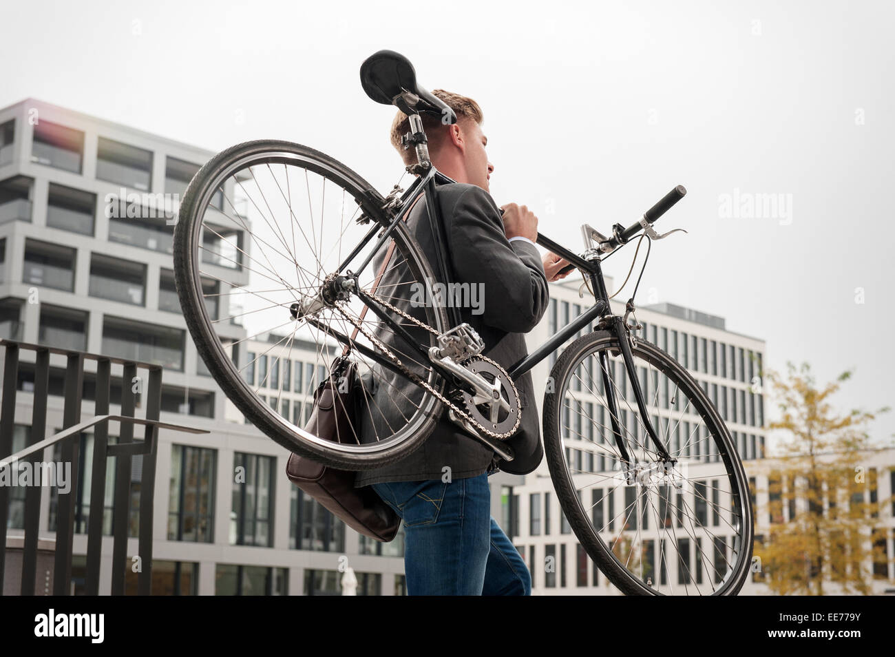 Young businessman carrying bicycle, Munich, Bavaria, Germany - Stock Image