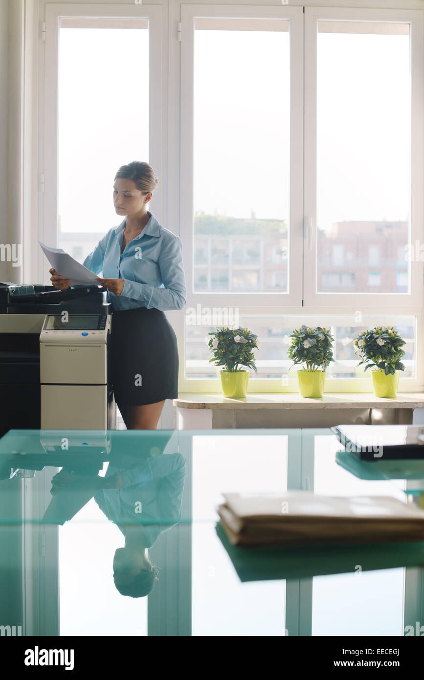 Female secretary working in office, copying document and paperwork with copy machine in modern office - Stock Image
