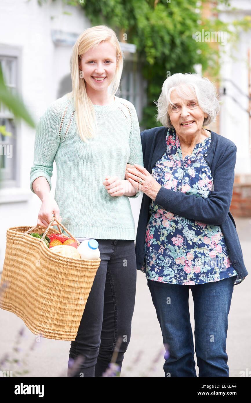 Teenage Girl Helping Senior Woman To Carry Shopping - Stock Image