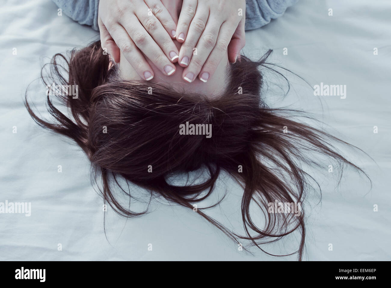 Woman lying on bed covering her eyes with hands - Stock Image