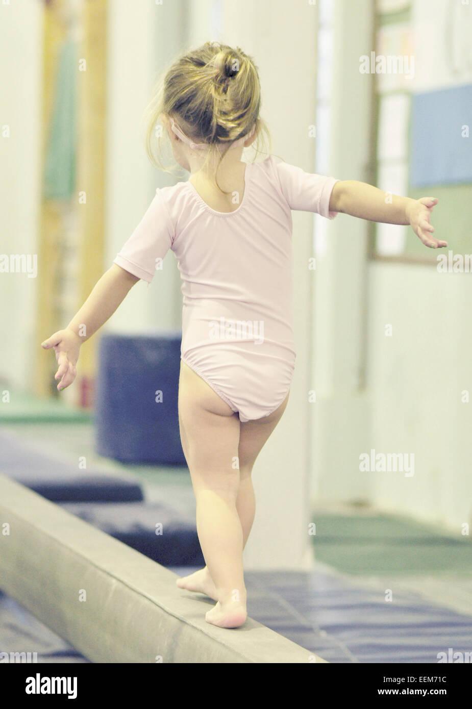 Girl (2-3) on balance bar - Stock Image