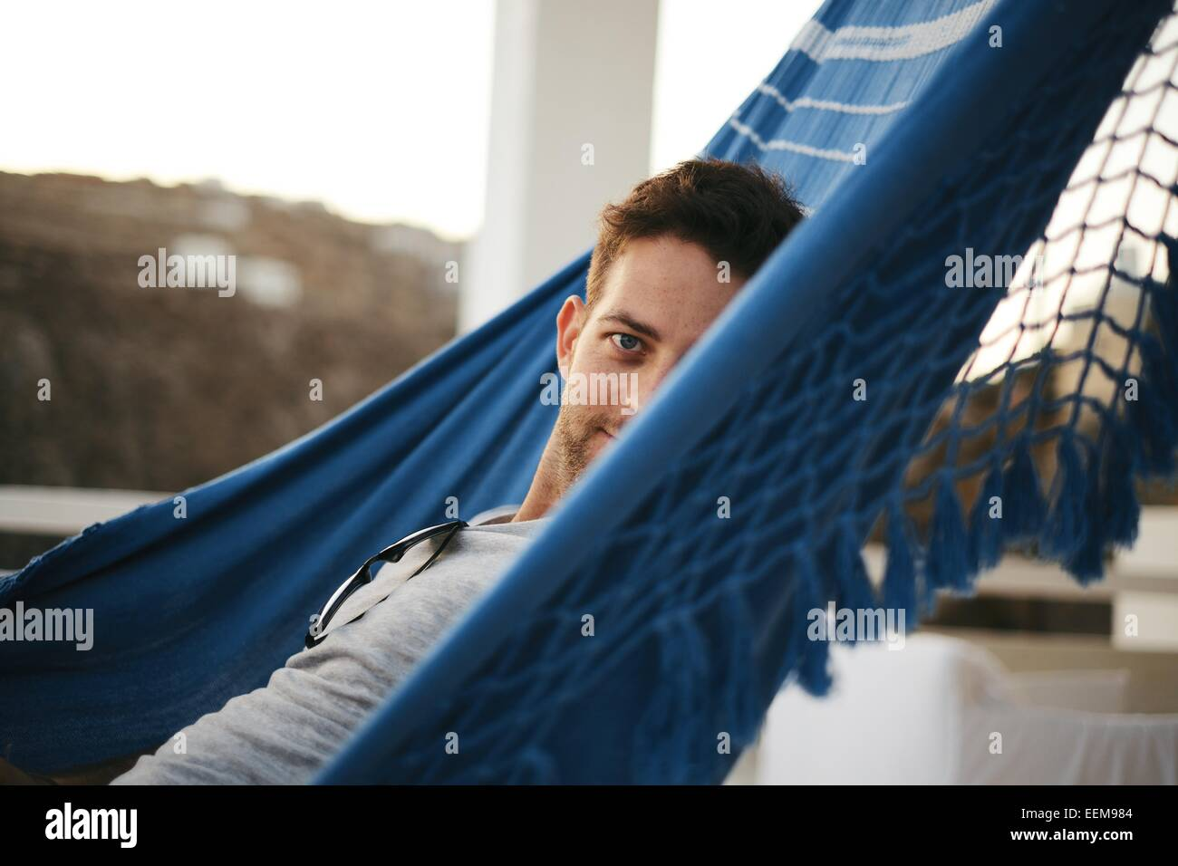 Man laying in hammock and looking at camera - Stock Image
