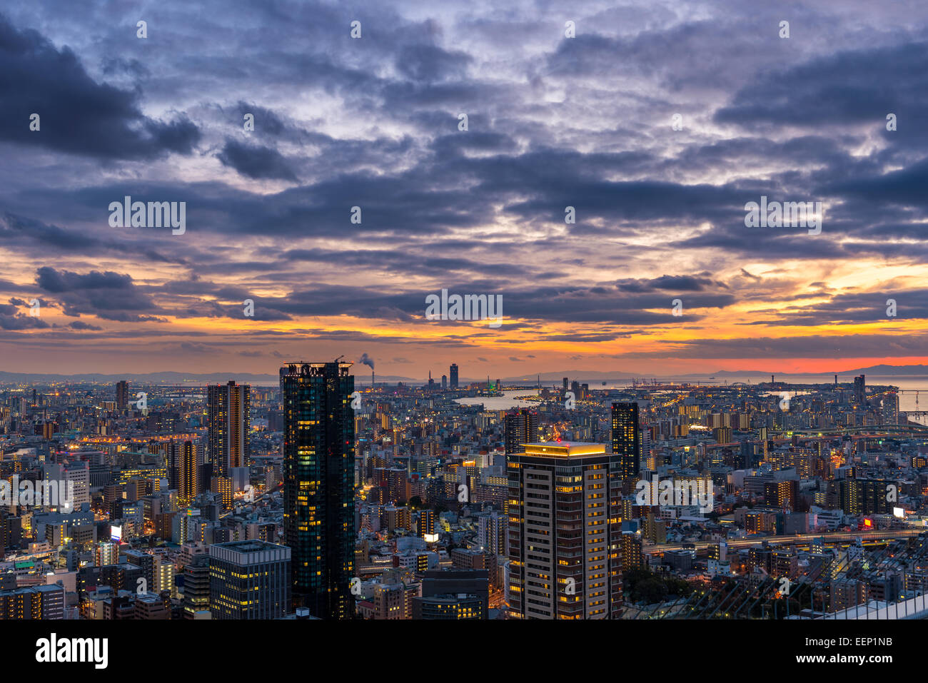 The sun sets over the vast cityscape of Osaka, Japan. - Stock Image