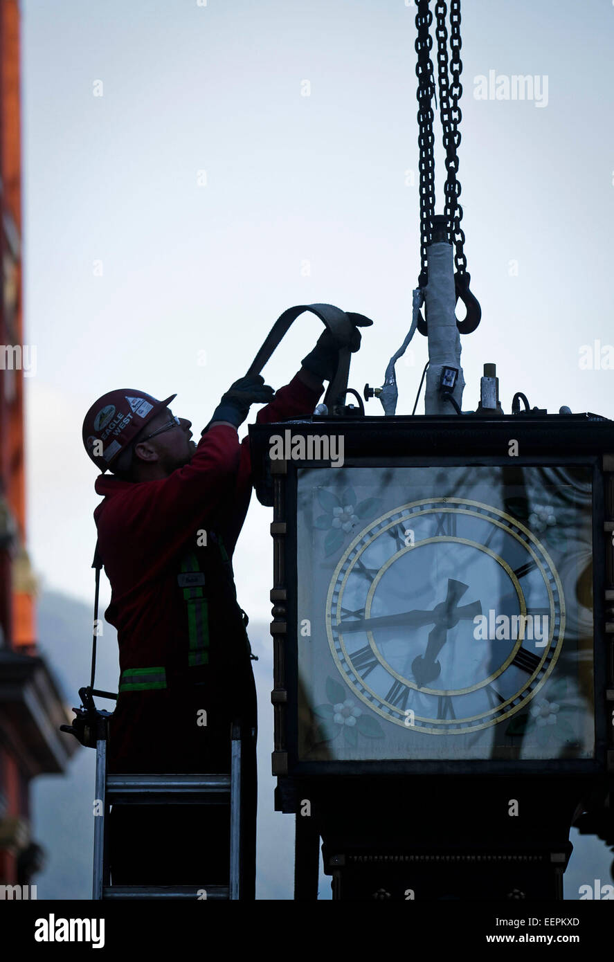 Canada, Vancouver. 21st Jan, 2015. A worker re-installs the steam clock to its original position at Gastown in Vancouver, - Stock Image