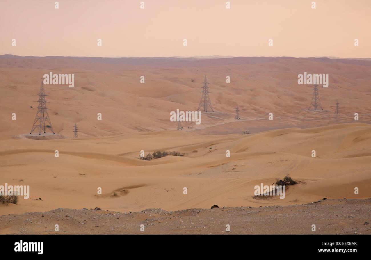 Sand Desert, Arabian Peninsula. Power lines going through desert. - Stock Image