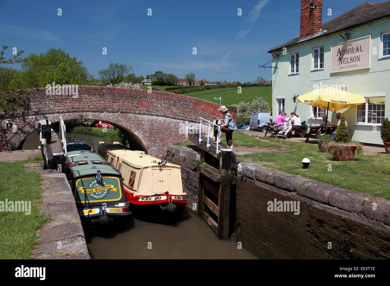 Two narrowboats entering double lock no. 3 on the Grand Union Canal by the Admiral Nelson pub at Braunston Stock Photo