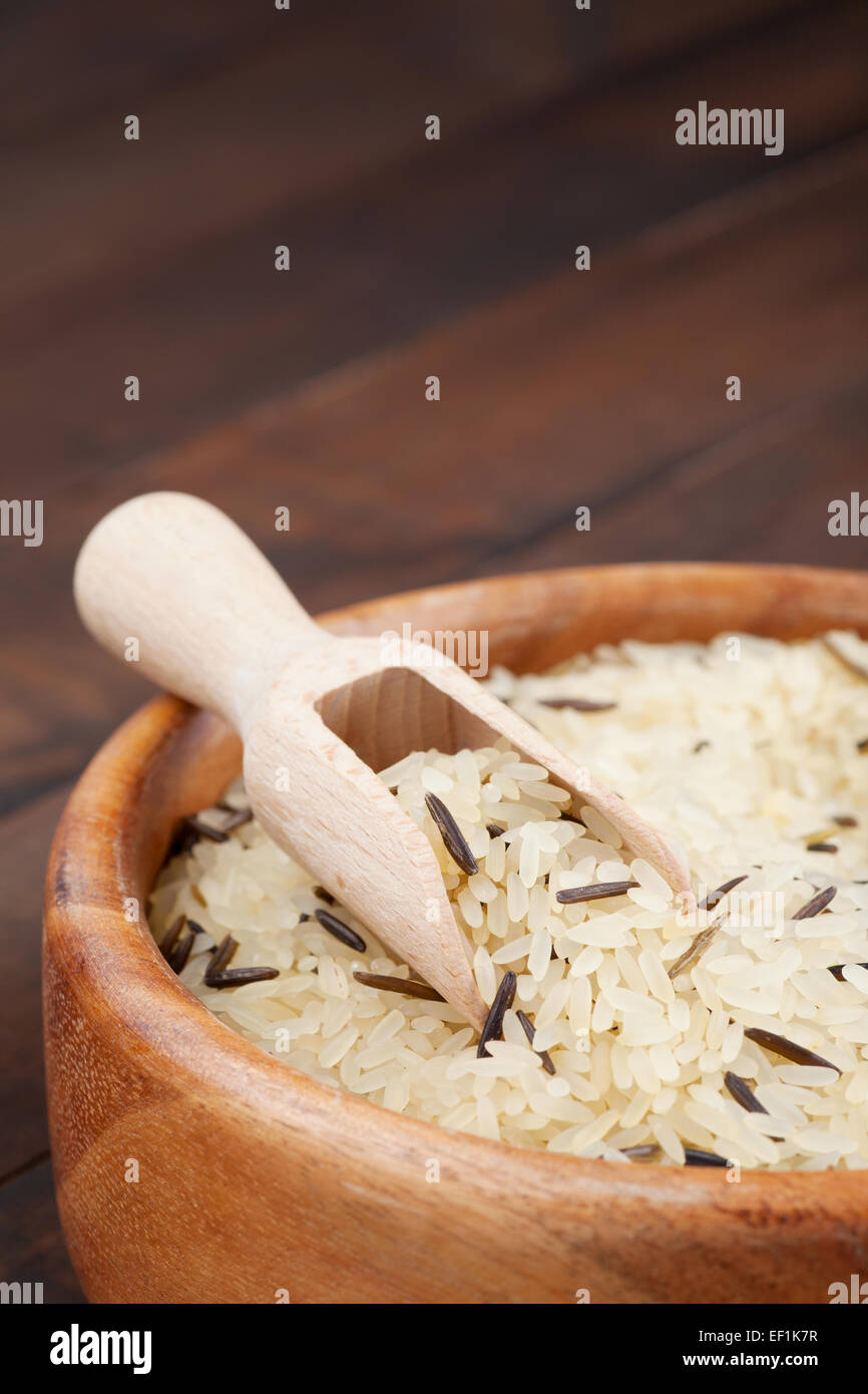 white and wild rice in wooden bowl on kitchen table - Stock Image