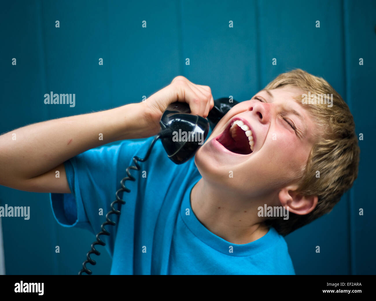 Child 10,11,12,13 laughing while talking on telephone, holding receiver - Stock Image