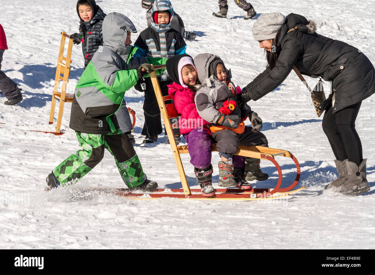 asian-children-and-their-mother-have-fun-using-a-dog-sled-as-a-toboggan-EF4B9E.jpg
