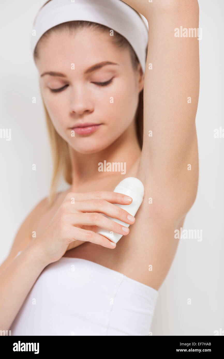 Beautiful woman applying deodorant Stock Photo