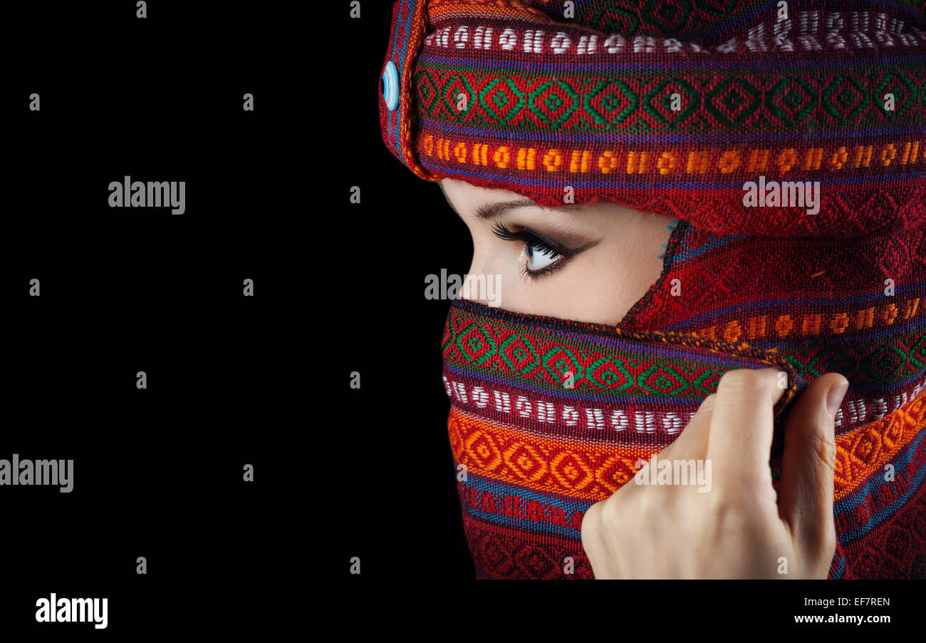 Oriental woman in turban covering her face on black background - Stock Image