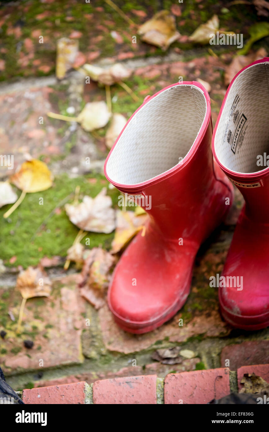 A pair of red Hunter wellington boots on a doorstep surrounded by leaves. Stock Photo