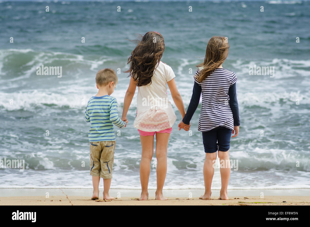 Bulgaria, Two girls (8-9) and boy (4-5) standing at by surf line holding hands looking at sea - Stock Image