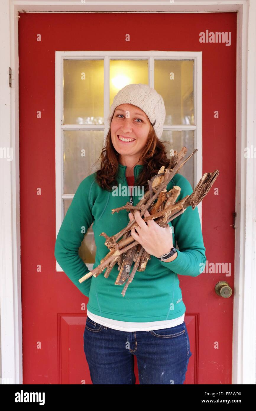 Young woman gathering firewood - Stock Image