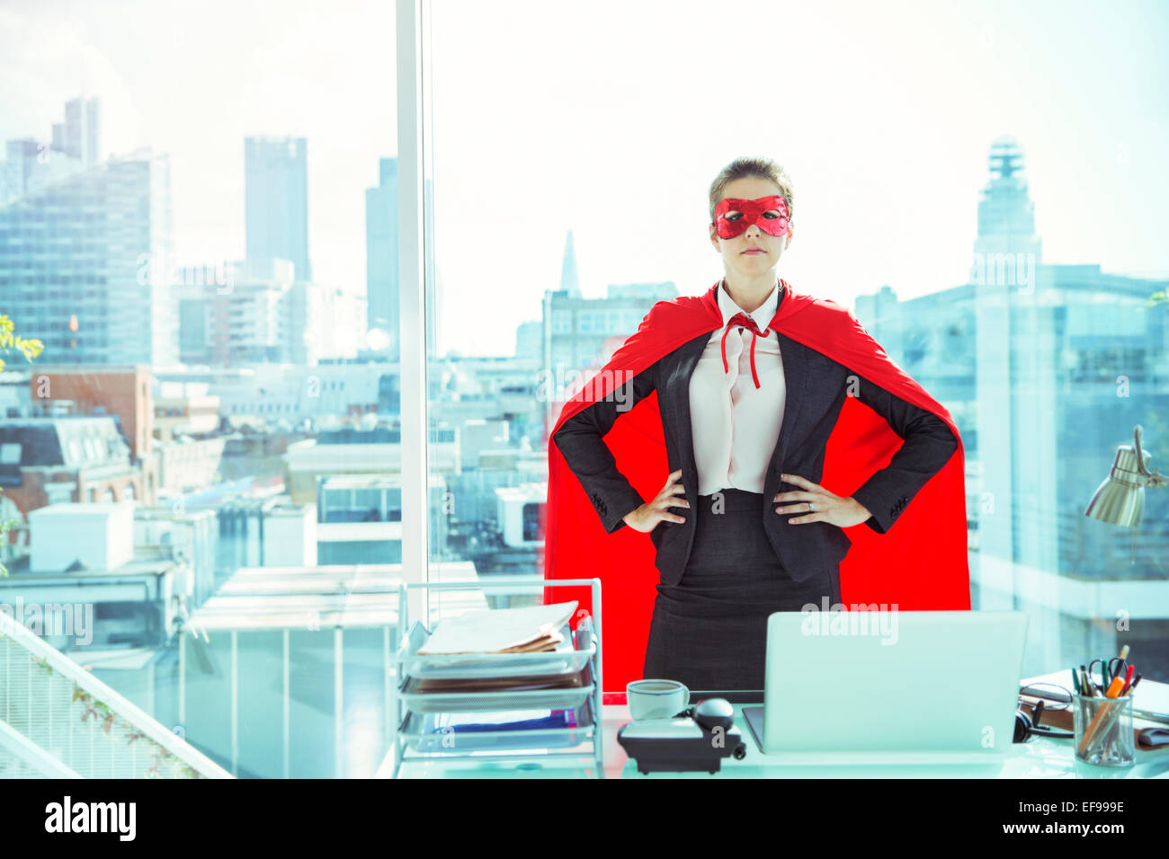 Businesswoman wearing cape and mask in office - Stock Image