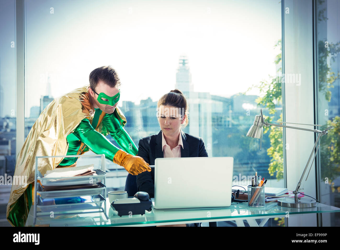 Superhero helping businesswoman working at office desk - Stock Image