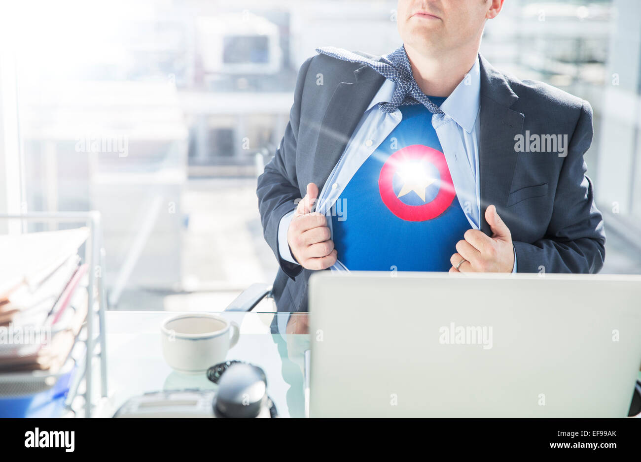 Businessman opening shirt to reveal superhero costume - Stock Image