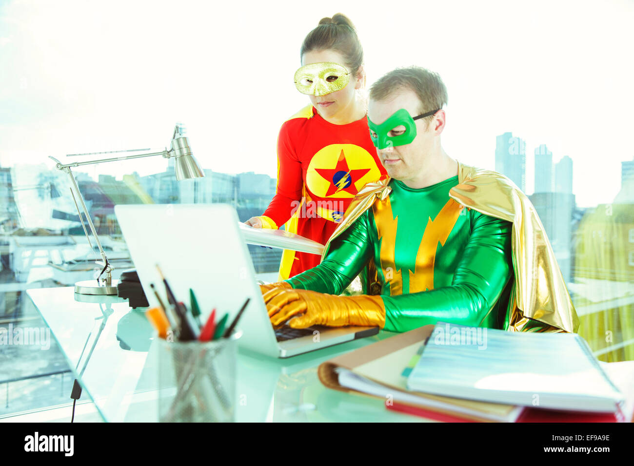 Superheroes working with laptop in office - Stock Image