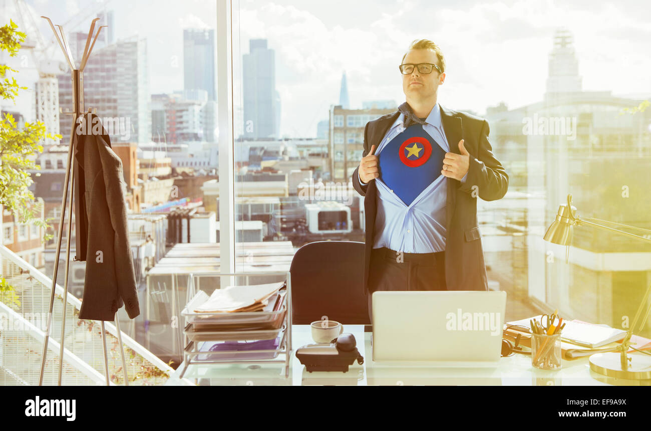 Businessman revealing superhero costume under suit - Stock Image