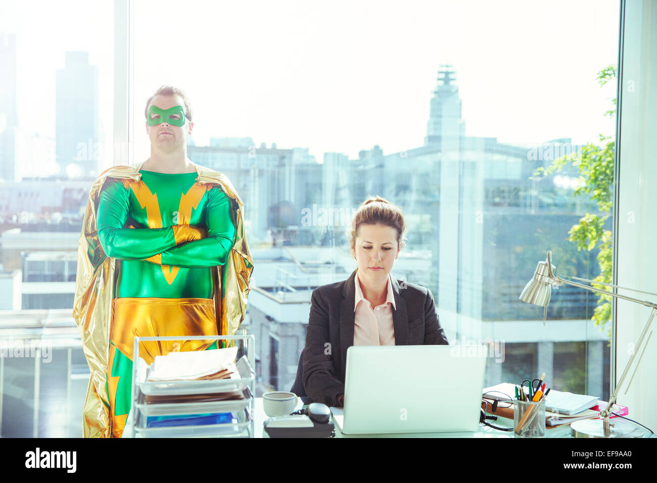 Superhero standing near businesswoman working in office - Stock Image