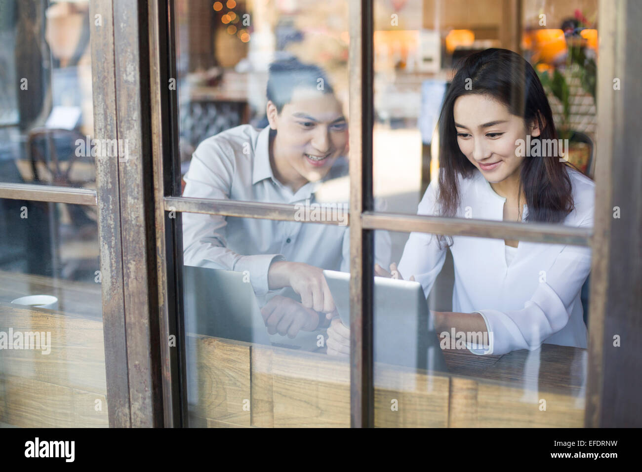 Young man and woman using digital tablet in cafe - Stock Image