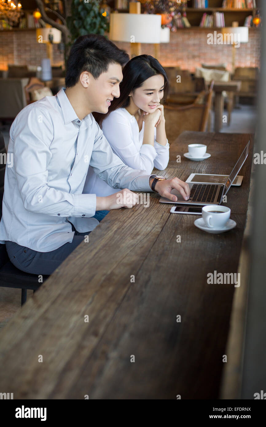 Young man and woman using laptop in cafe - Stock Image