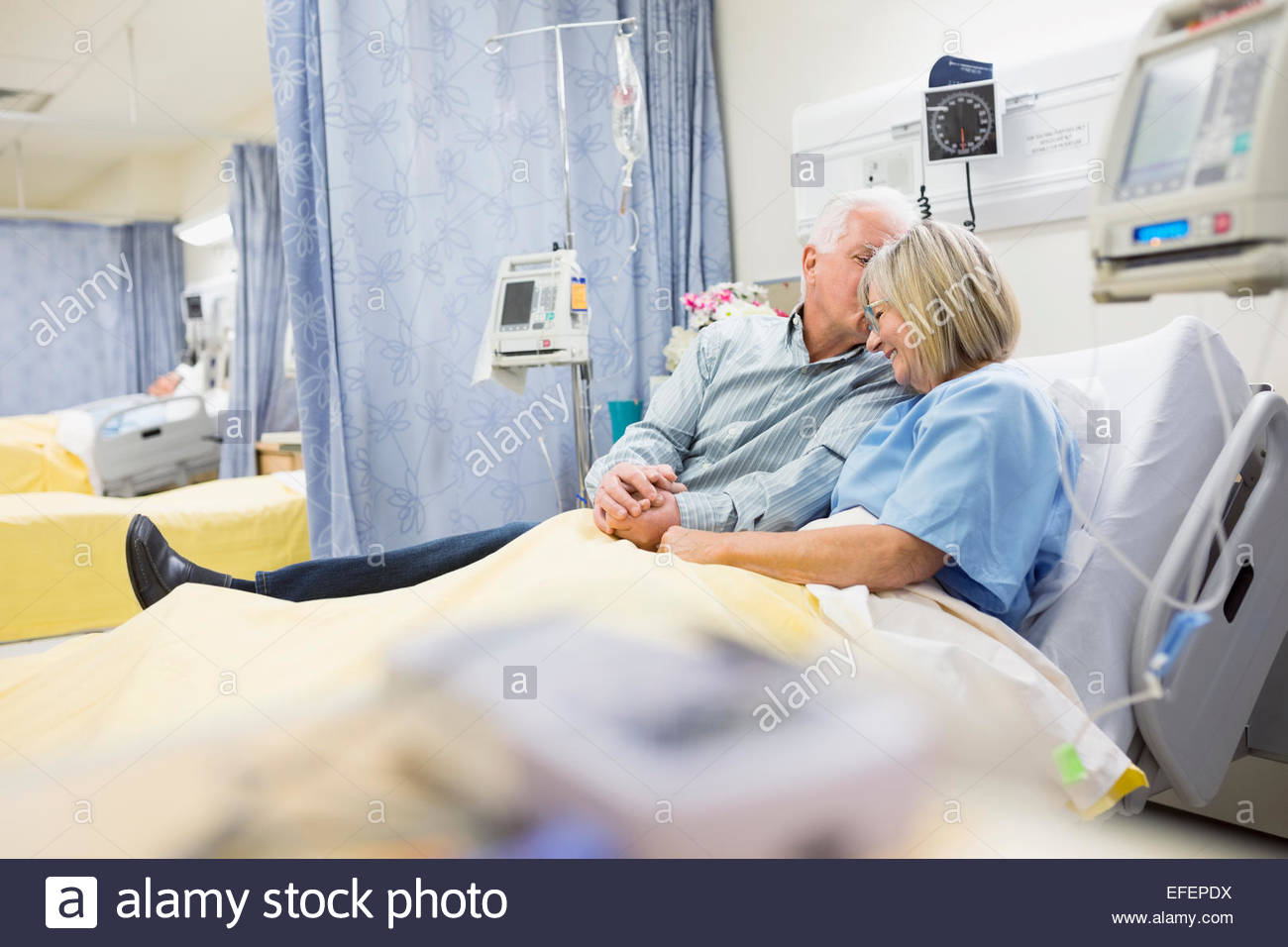 Husband comforting wife in hospital bed - Stock Image