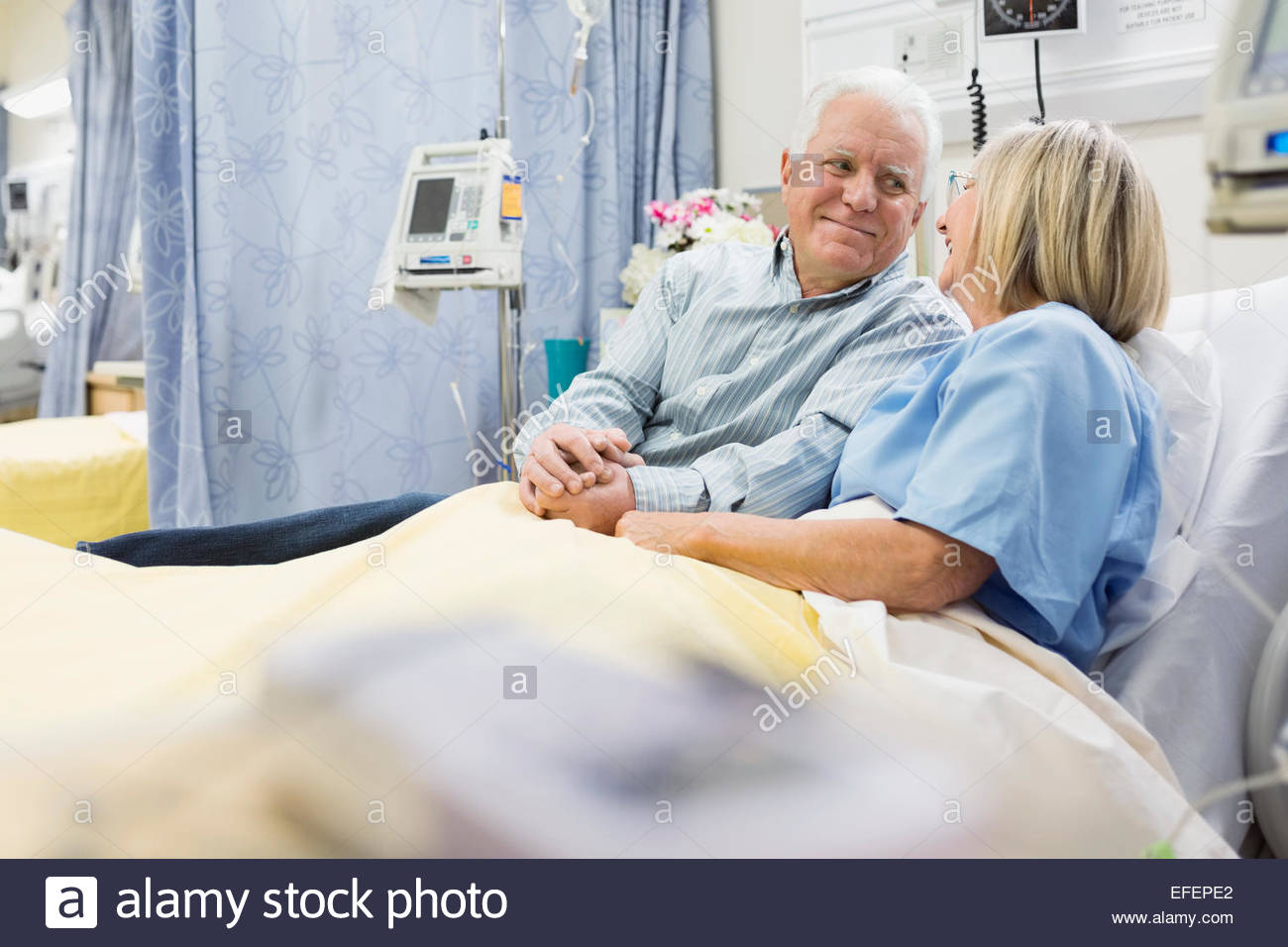 Husband and wife holding hands in hospital bed - Stock Image