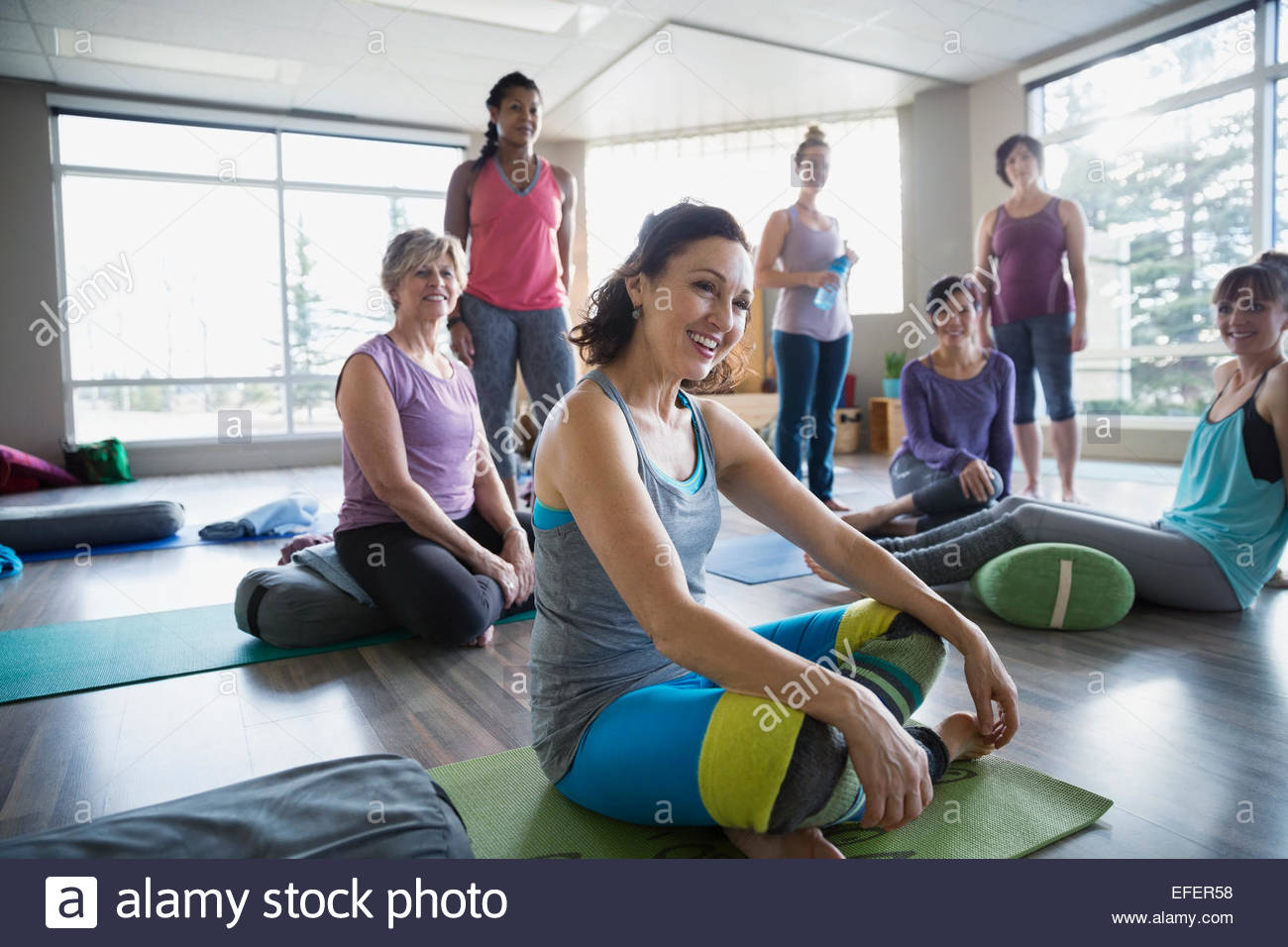 Smiling women in restorative yoga class - Stock Image