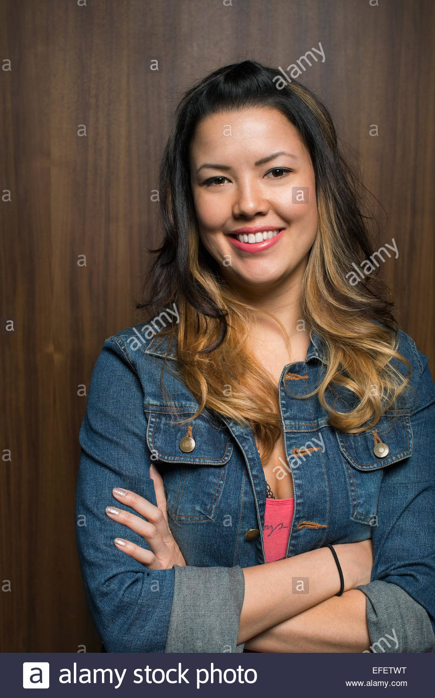 Portrait of smiling woman wearing denim jacket - Stock Image