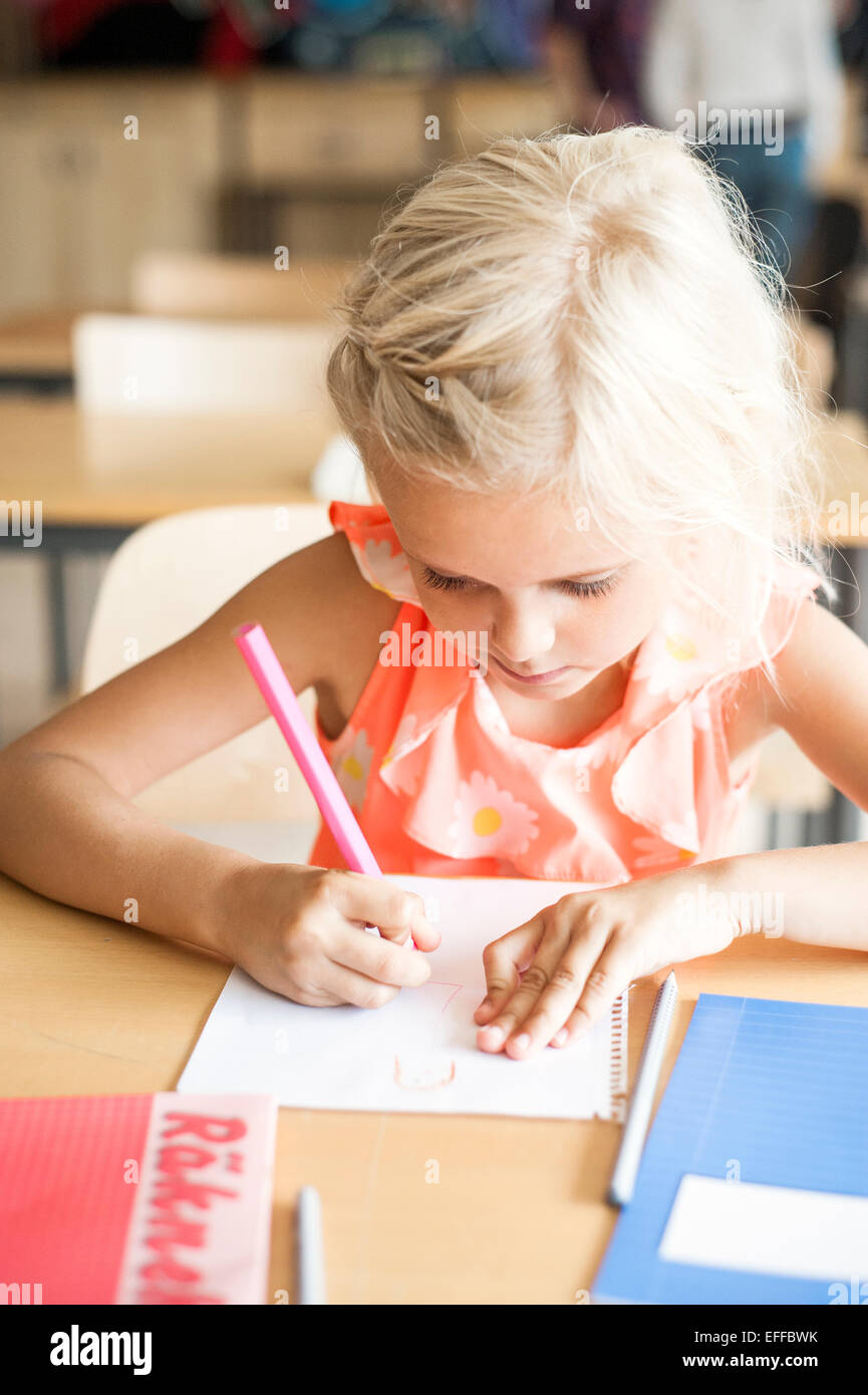 Cute girl drawing during art class - Stock Image