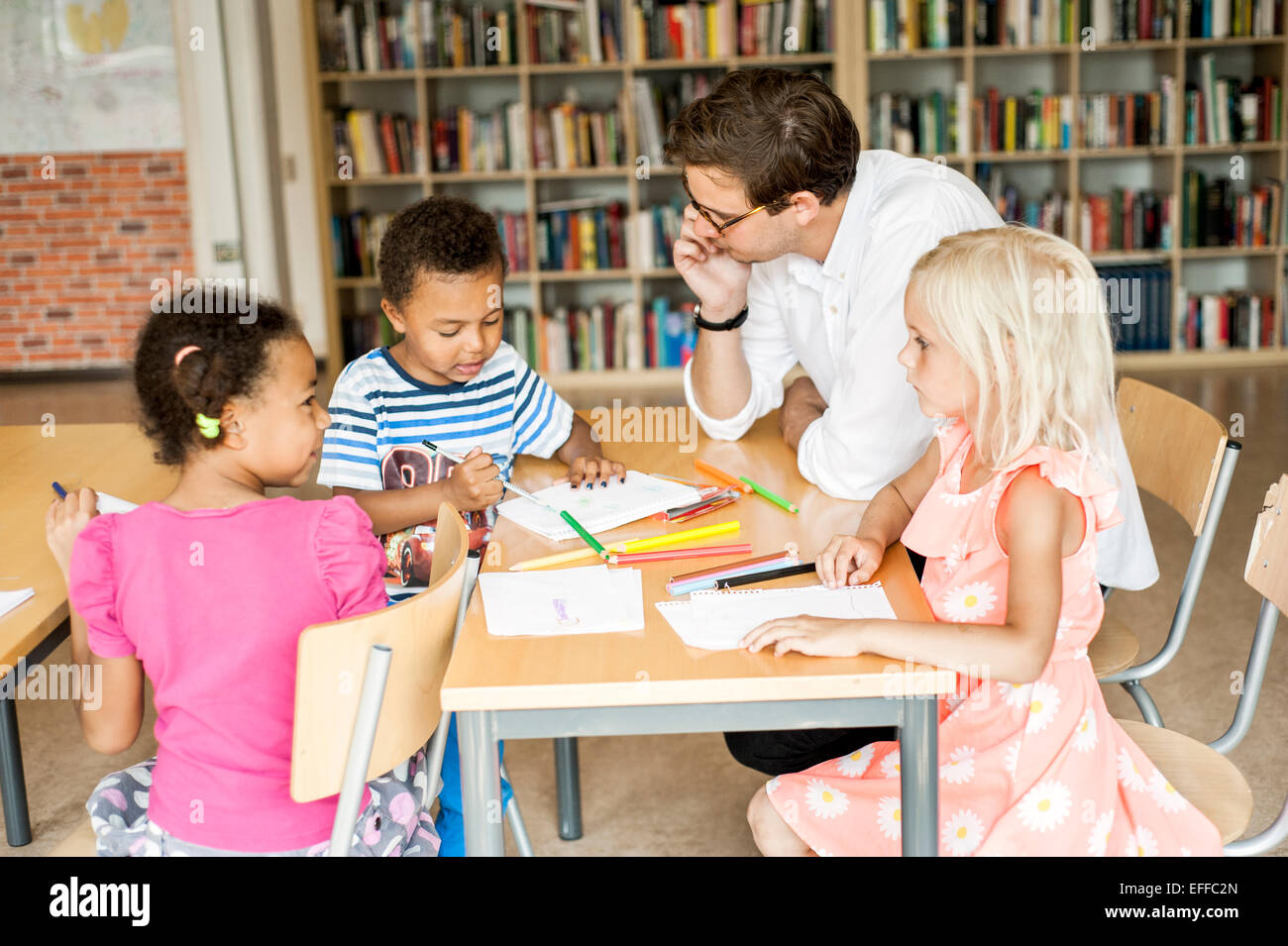 Teacher with students during art class - Stock Image