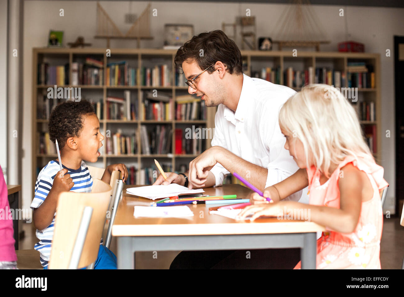 Male teacher teaching students during art class - Stock Image