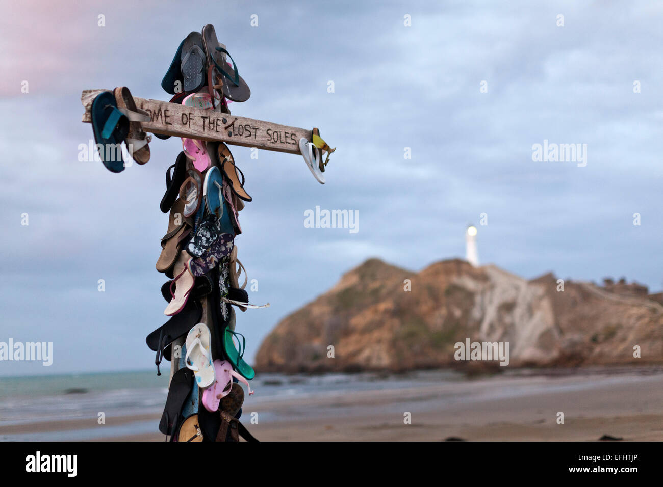 Cross with sandals, Home of the lost soles, humour on the beach, Castle Point, East coast, Wairarapa, North Island, - Stock Image