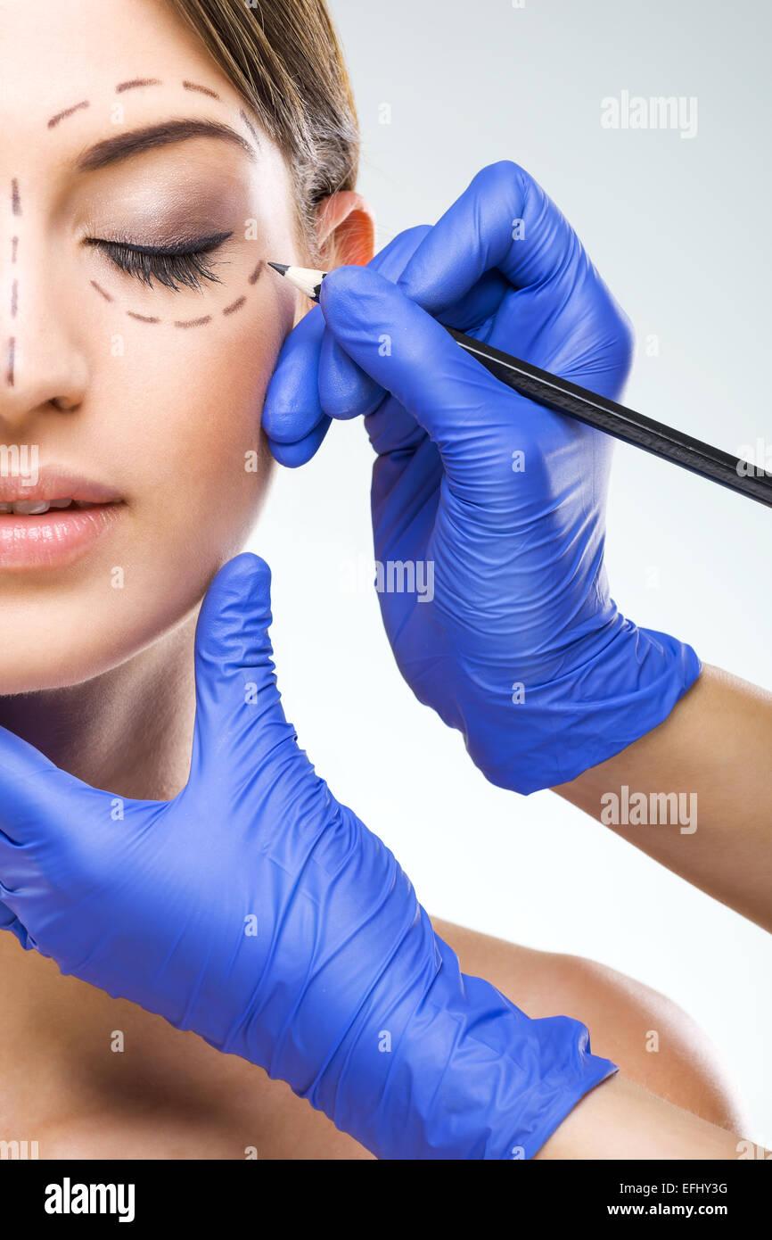 Beautiful woman half face photo plastic surgery, plastic surgeon hands - Stock Image