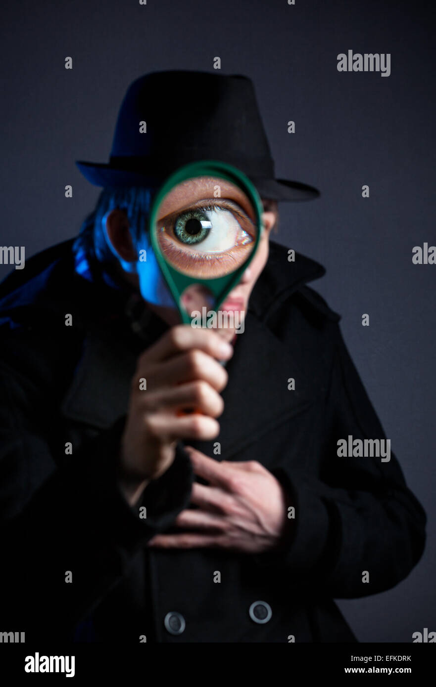 Man in black hat with magnifier glass at dark background - Stock Image