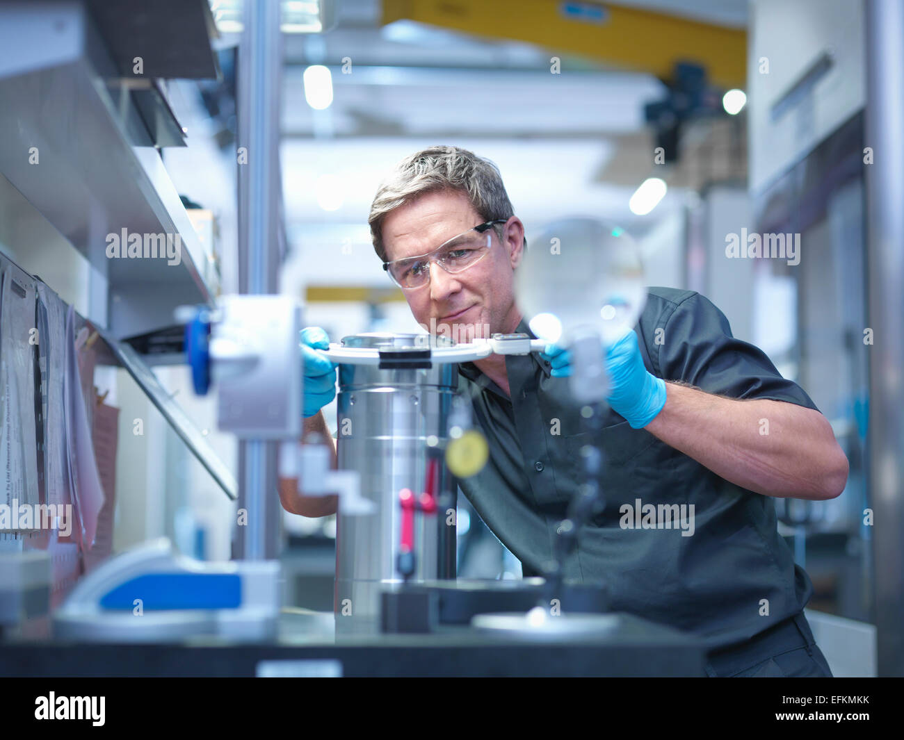 Engineer inspecting part at work station in engineering factory - Stock Image