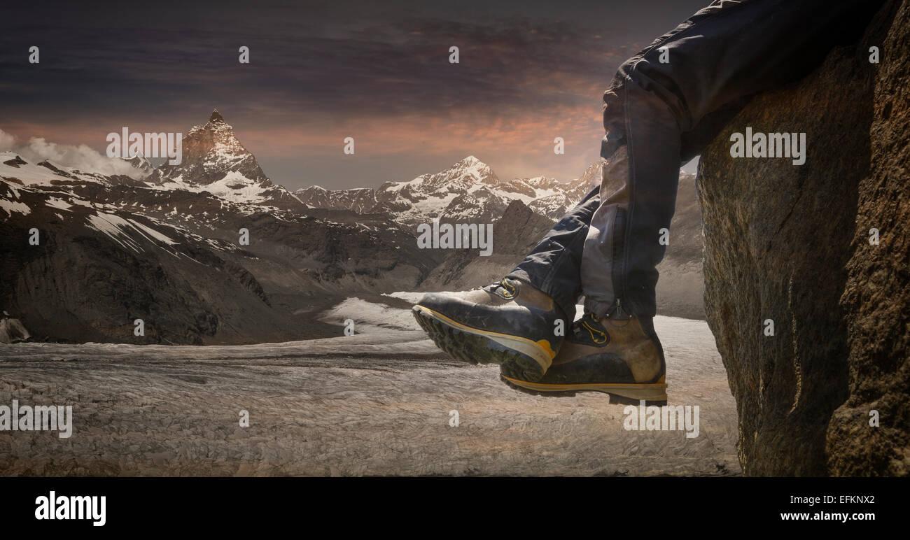 Legs of male climber dangling over rock edge, Zermatt, Matterhorn, Canton Wallis, Switzerland - Stock Image