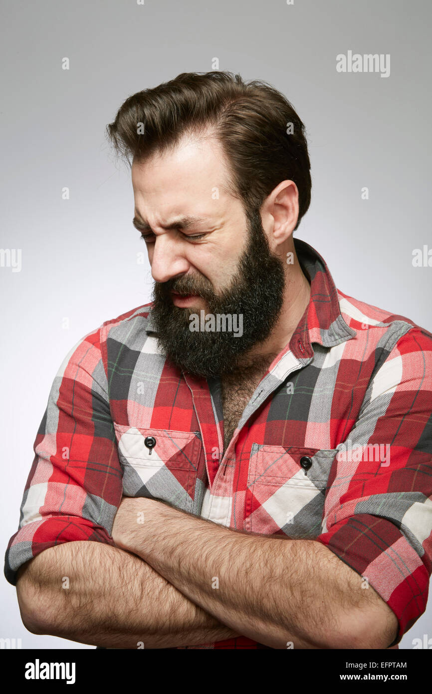 Studio portrait of anguished bearded young man with arms folded - Stock Image