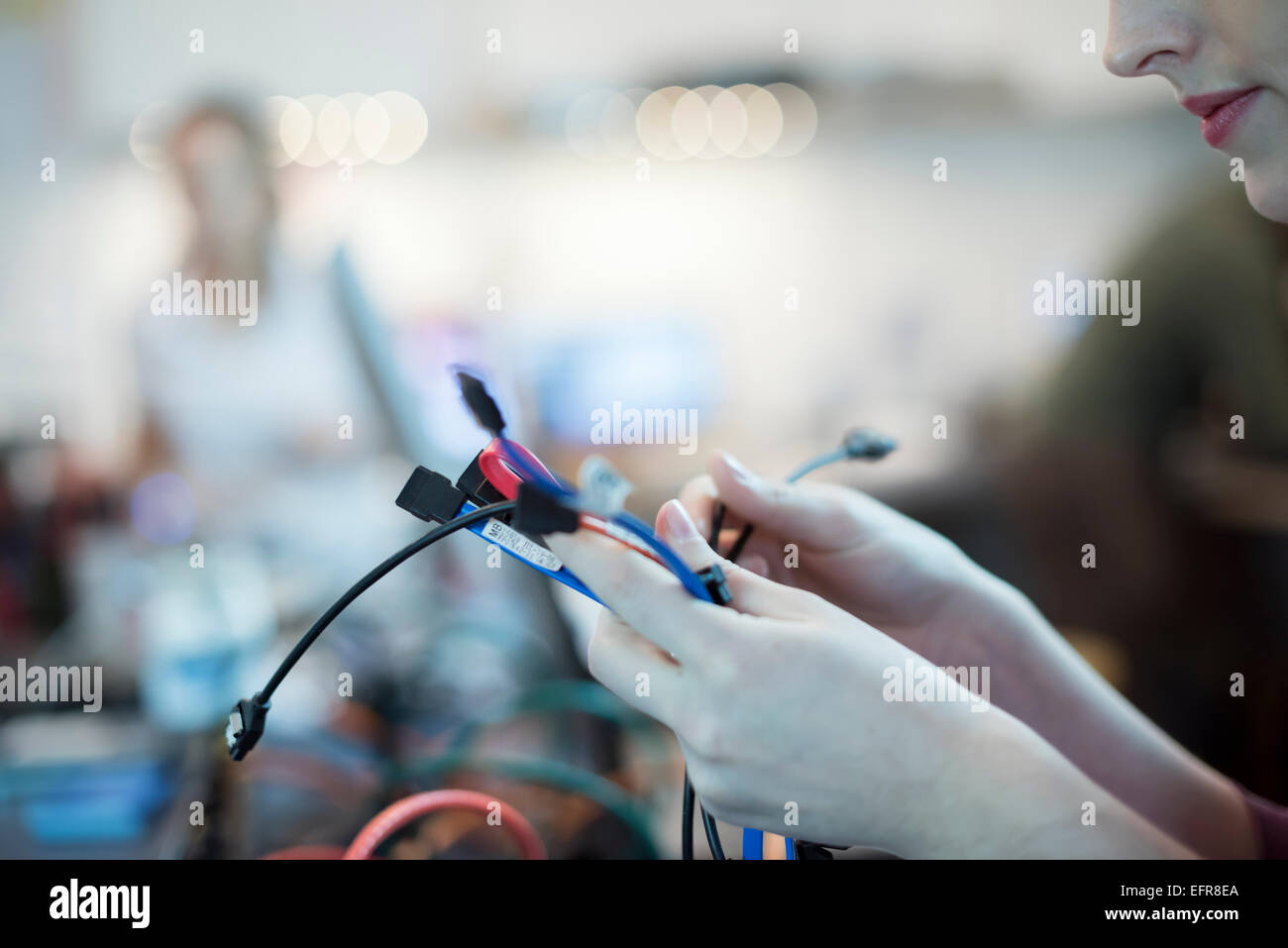 A young woman using connecting cables and usb leads in a computer repair shop. - Stock Image