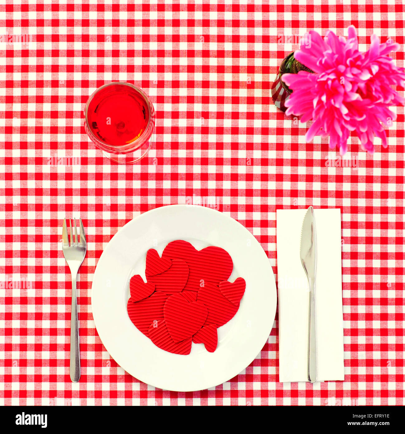 high-angle shot of a plate full of red hearts with different size on a set table with a checkered red and white - Stock Image