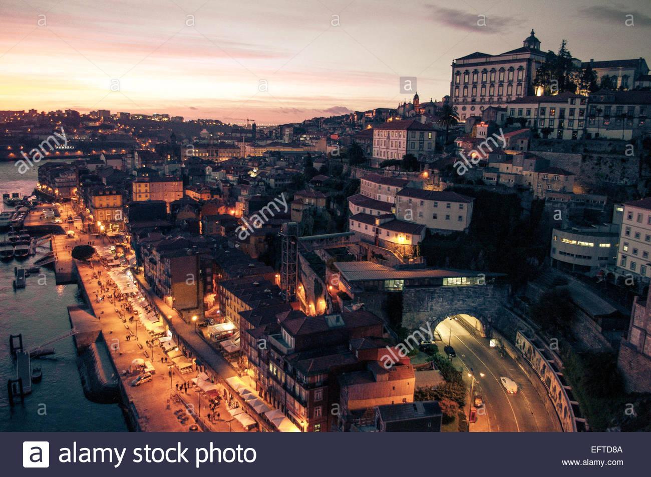 Illuminated riverfront cityscape - Stock Image