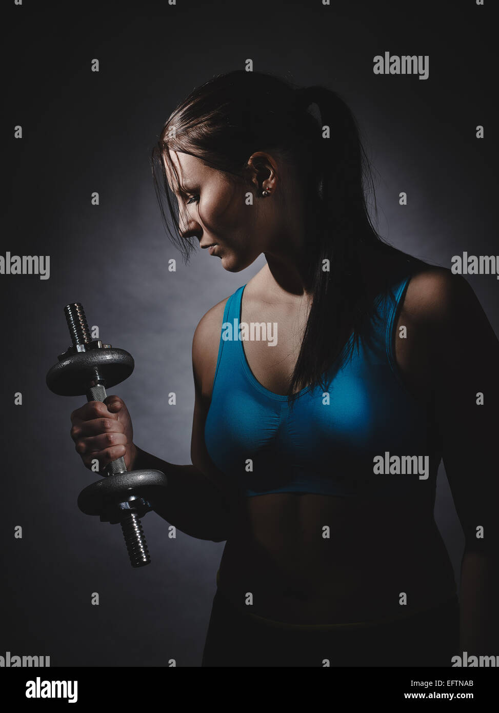 Weightlifting, young woman wearing sportswear and she exercise, studio shot, dark background - Stock Image