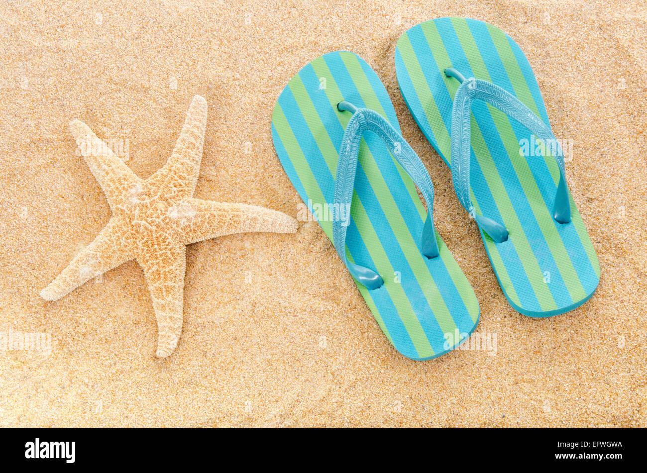 striped-flip-flops-rubber-sandals-beach-slippers-on-sandy-beach-sea-EFWGWA.jpg