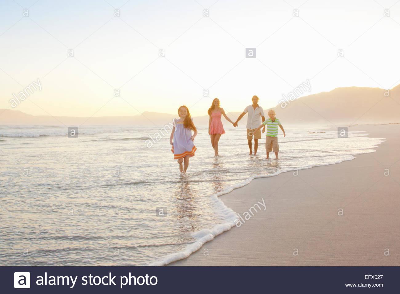 Happy family holding hands on sunny beach - Stock Image