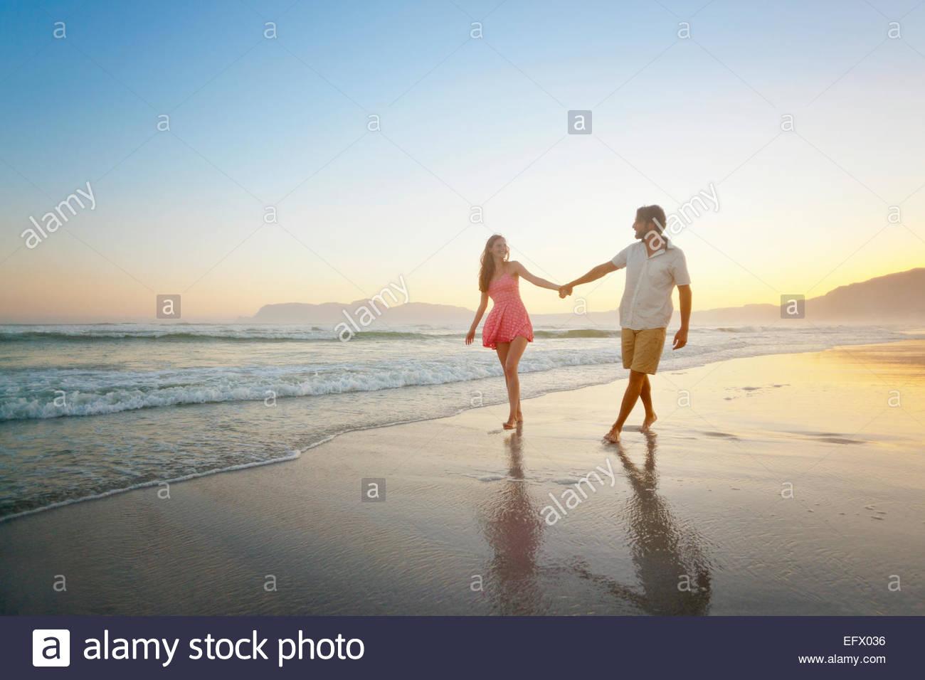 Couple, holding hands, walking along sunny beach - Stock Image