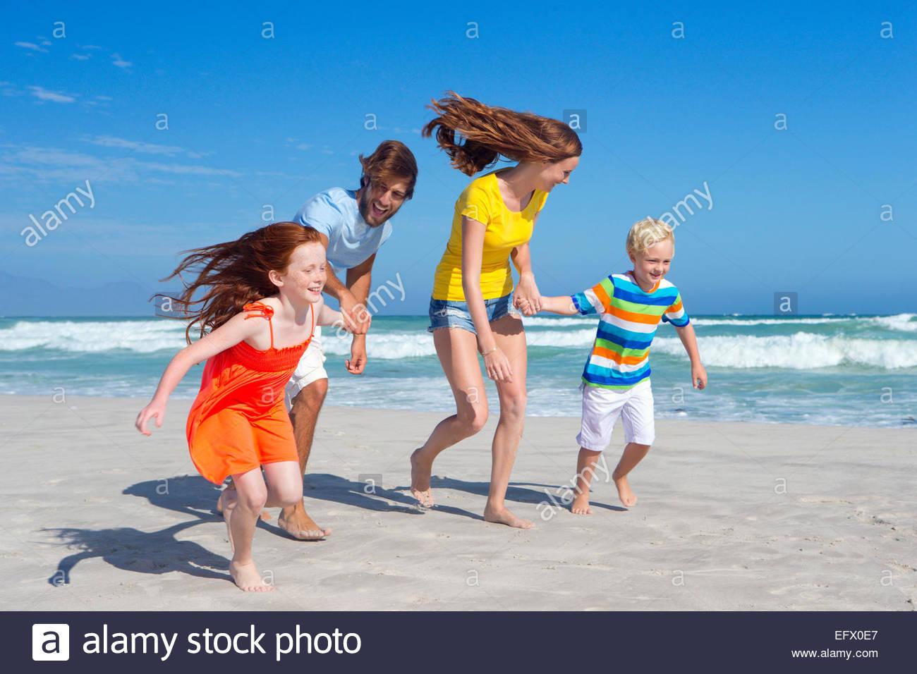 Happy family holding hands, running along sunny beach - Stock Image