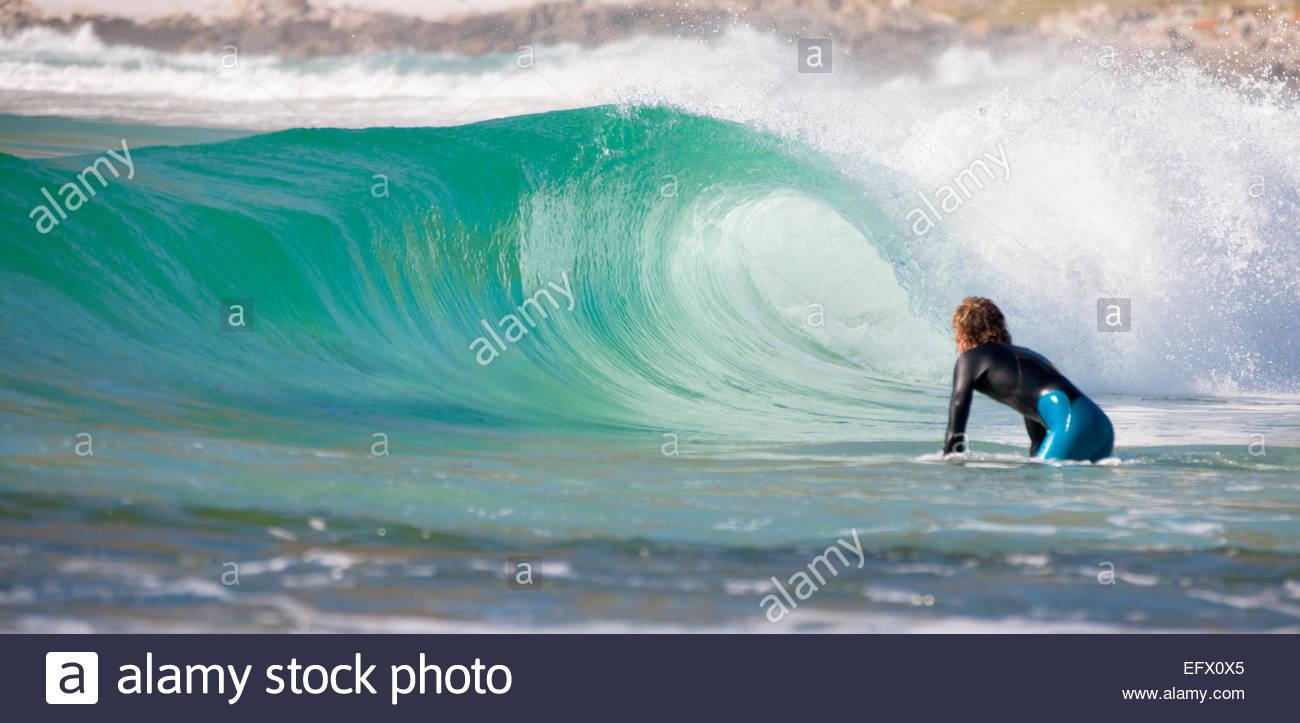 Surfer getting ready to ride wave - Stock Image