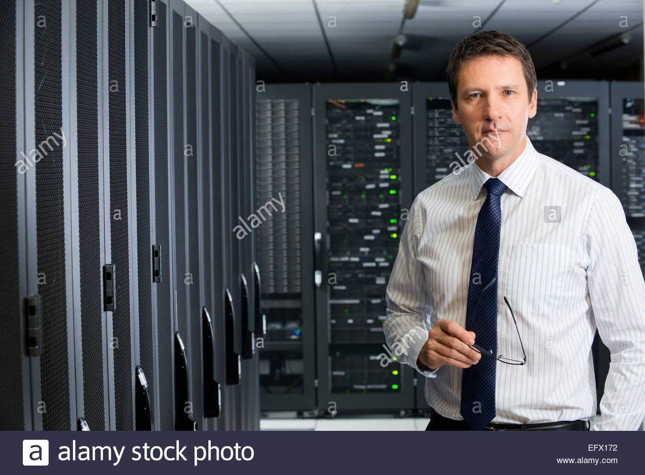 Manager holding glasses, looking at camera, in server room - Stock Image