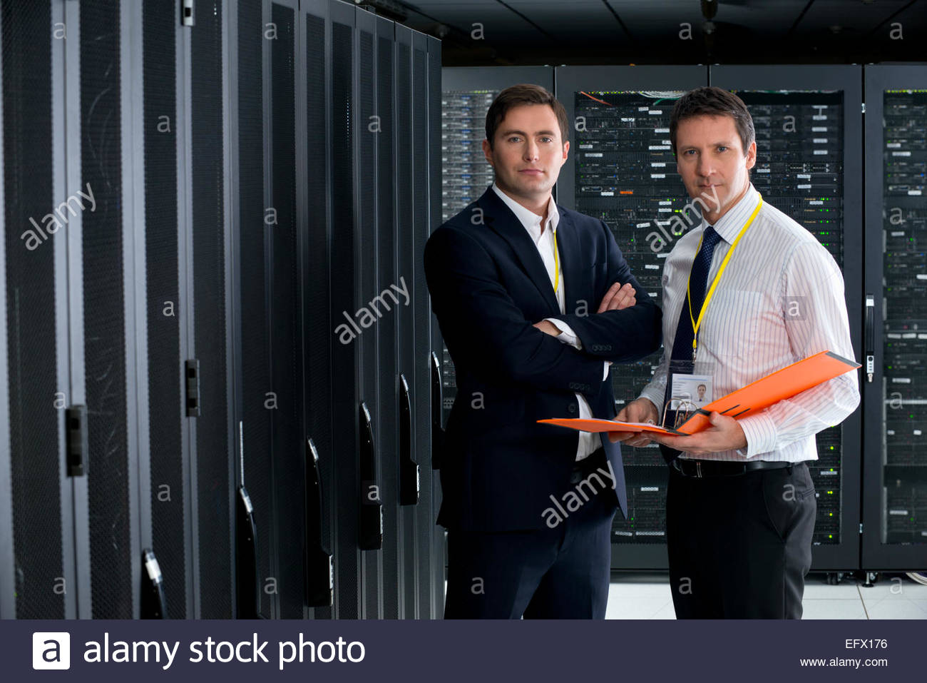 Two managers, looking at camera, in server room - Stock Image